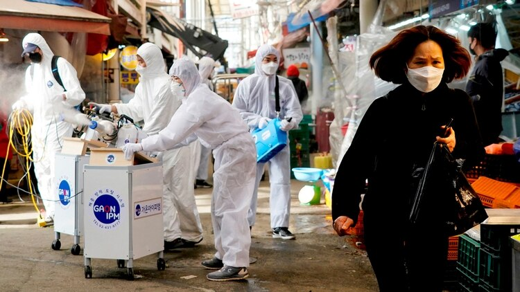 Una mujer coreana camina por Seúl con un barbijo, mientras efectivos sanitarios desinfectan las calles - REUTERS/Kim Hong-Ji TPX IMAGES OF THE DAY