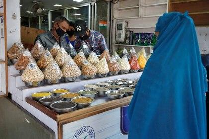 Una mujer musulmana compra fruta seca en una tienda en la víspera del mes sagrado de ayuno del Ramadán en Ahmedabad, India, el 24 de abril de 2020. REUTERS/Amit Dave