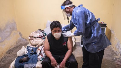 Paramedic Jorge Lino, 52, checks a man with symptoms of COVID-19, in Ciudad Nezahualcoyotl, Mexico State, Mexico, on June 22, 2020 during the novel coronavirus pandemic. - Paramedics receive calls from COVID-19 patients or suspected cases, but as the night falls in Mexico, situations of death and violence await them. (Photo by Pedro PARDO / AFP)