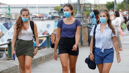 Young people wear masks as they walk on the street following a government decree that face coverings must be worn between 6 p.m. and 6 a.m. in areas close to bars and pubs and where gatherings are more likely, due to the coronavirus disease (COVID-19) outbreak, in Naples, Italy August 17, 2020. REUTERS/Ciro De Luca