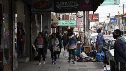 Varias personas caminan por la Avenida Ignacio Arieta, en una importante zona comercial del centro de San Justo
