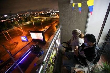 Gente mira una película que se exhibe en la calle, desde el balcón de su apartamento, en medio del brote de la enfermedad por coronavirus en Bogotá (REUTERS/Luisa Gonzalez)