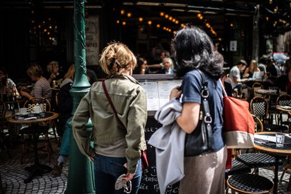 Clientes examinan un menú de un restaurante parisino que reabrió sus puertas este lunes.