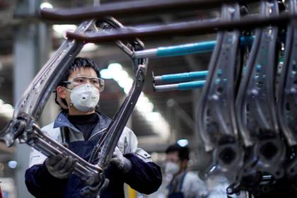 Un empleado con una máscara facial trabaja en una línea de ensamblaje de asientos de automóviles en la fábrica Yanfeng Adient en Shanghai, China, en una foto tomada el 24 de febrero de 2020. (REUTERS / Aly Song /archivo)