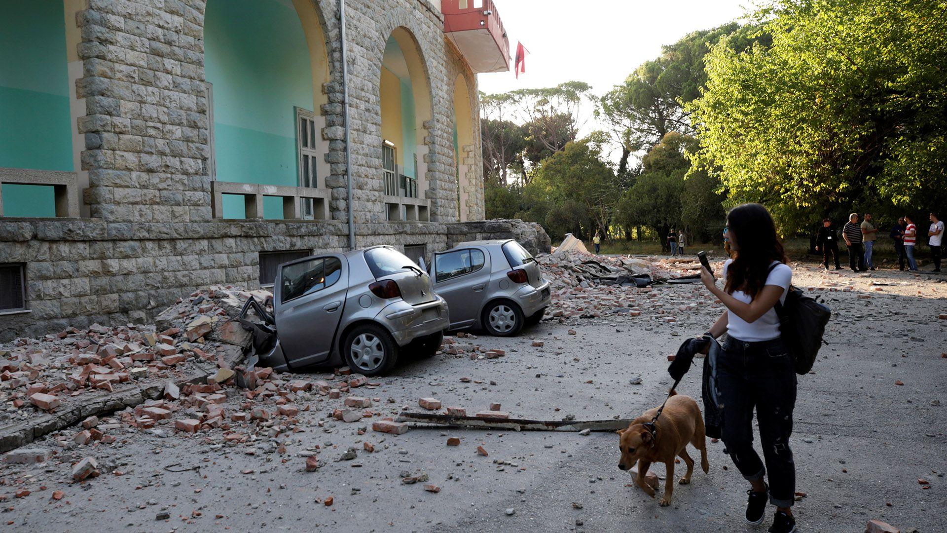 Una mujer pasa cerca de los destrozos por el terremoto(REUTERS/Florion Goga)