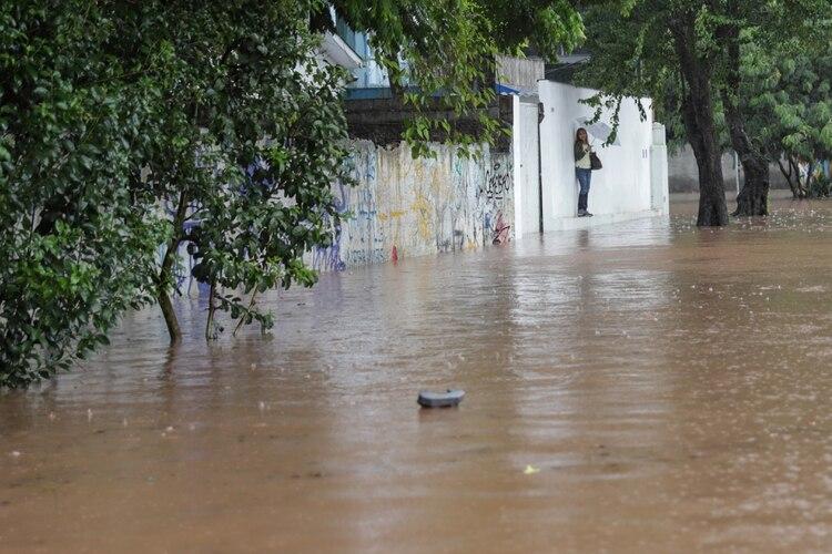 Una mujer está parada junto a una pared junto a una calle inundada después de las fuertes lluvias en el barrio de Butanta en Sao Paulo, Brasil, 10 de febrero de 2020. REUTERS / Rahel Patrasso