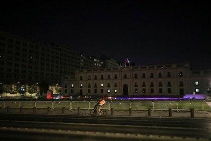 Imagen de archivo de un repartidor pasando en su bicicleta frente al palacio presidencial chileno de La Moneda, en pleno brote de coronavirus en Santiago, Chile, el 27 de marzo de 2020. REUTERS/Pablo Sanhueza