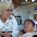 zzzzinte1(FILES) Picture taken 11 December, 2005 in La Plata, province of Buenos Aires, Argentina of Ofelia Wilhelm de Fernandez (L), mother of Argentina's president elect Cristina Fernandez de Kirchner, talking during a football match with other supporters of her favorite team Gimnasia y Esgrima de La Plata, wearing the club's jersey autographed by the team players. Argentina's current first lady, Cristina Kirchner, has won a mandate to take over from her husband as president, according to a near-complete count Monday of ballots from a weekend election. AFP PHOTO/ALEJANDRO PAGNIzzzz