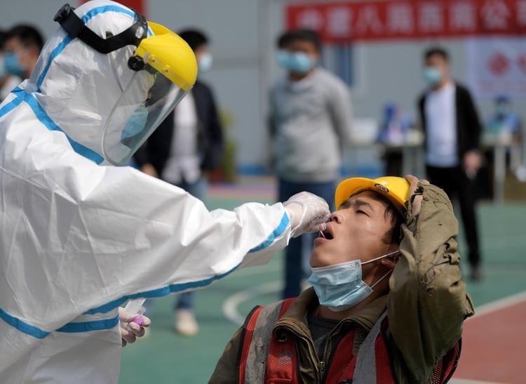 FOTO DE ARCHIVO: Un trabajador con un traje protector recoge un hisopo de un trabajador de la construcción para una prueba de ácido nucleico en Wuhan, provincia de Hubei, el epicentro del brote de la enfermedad del coronavirus (COVID-19) en China, (China Daily vía REUTERS)