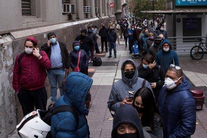 Un grupo de personas hace fila para acceder a un banco en el centro de Santiago, Chile, en pleno brote de coronavirus (EFE/Alberto Valdés)