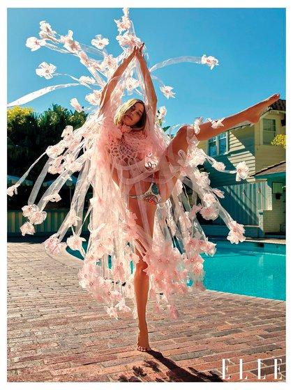 A orillas de su piscina, luce un vestido de Noir Kei Ninomiya y una bikini con estampado de búlgaros de Versace (Revista Elle)
