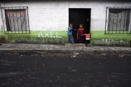 Niños afuera de su casa tras la erupción del volcán Pacaya (Orlando  ESTRADA / AFP)