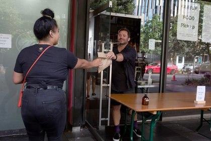 Un cliente recolecta comida para llevar a Nueva Zelanda, para aliviar las estrictas regulaciones implementadas para frenar la propagación de la enfermedad por coronavirus (COVID-19) en Auckland, Nueva Zelanda  [28 de abril de 2020] (Reuters/ Ruth McDowall  NO RESALES. NO ARCHIVES)