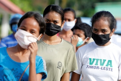 Mujeres con máscaras protectoras caminan por una calle en Dili, Timor Oriental, el 16 de abril de 2020 (REUTERS/Lirio da Fonseca)