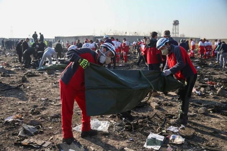Miembros de la Media Luna Roja revisan bolsas de plástico en el sitio donde el avión de Ukraine International Airlines se estrelló tras ser abatido por un misil antiaéreo (Reuters)