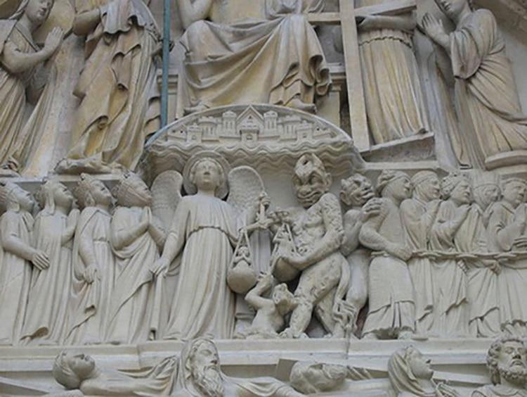 Detalle del pórtico central: el arcángel Miguel pesa las almas. Al otro lado, el diablo espera. Desde abajo, asoma un pequeño demonio que trata de inclinar la balanza…