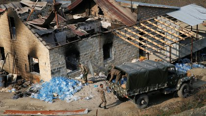 Ethnic Armenian soldiers load bottles with water into the truck next to a burnt house in the village of Knaravan, located in a territory which is soon to be turned over to Azerbaijan under a peace deal that followed the fighting over the Nagorno-Karabakh region, November 15, 2020. REUTERS/Stringer