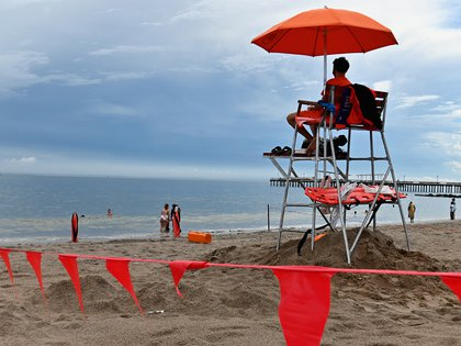 A lifeguard sits at Coney Island beach on July 1, 2020 in New York City, as beaches reopen to the public for swimming. - Hospitalizations and infections continue to hit new lows but officials fear a spike in rates elsewhere could cause an uptick in New York as it slowly reopens business and other activities. (Photo by Angela Weiss / AFP)