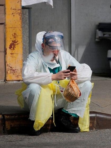 Un trabajador de la salud se sienta en la acera mientras usa un dispositivo de vapeo durante un descanso fuera del Centro Médico Maimonides, en el barrio de Brooklyn, en Nueva York (REUTERS/Brendan Mcdermid)