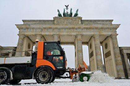 Un vehículo retirando nieve de la Puerta de Branderburgo, en Berlín (John MACDOUGALL / AFP)