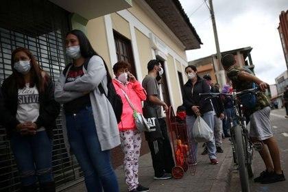 Personas usan máscarillas mientras hacen cola para ingresar a un supermercado durante el aislamiento obligatorio decretado por el gobierno colombiano, en Soacha.
