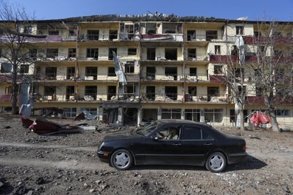 A man drives a car past a damaged building following recent shelling in the town of Shushi (Shusha), in the course of a military conflict over the breakaway region of Nagorno-Karabakh, October 29, 2020. Vahram Baghdasaryan/Photolure via REUTERS ATTENTION EDITORS - THIS IMAGE HAS BEEN SUPPLIED BY A THIRD PARTY.