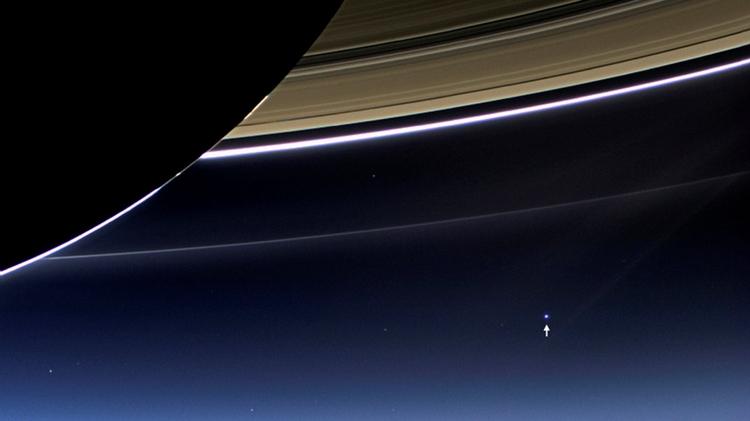 En esta foto del 19 de julio de 2013 se puede ver a Saturno en primer plano y a la Tierra como un punto distante con brillo. REUTERS/NASA/Handout via Reuters/File Photo