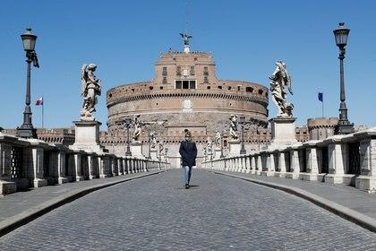 Una mujer con un barbijo pasea frente a Castel Sant'Angelo, en Roma. (REUTERS/Remo Casilli)