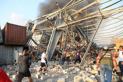 Personas caminan entre los escombros (AFP)