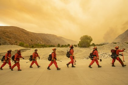 Bomberos llegan a la escena del incendio de Water, a unas 20 millas del incendio de Apple en Whitewater, California (AFP)