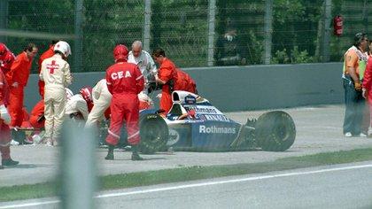 El momento en que Ayrton Senna es asistido fuera de su vehículo Williams tras chocar contra el muro de contención a más de 200 kilómetros por hora (Shutterstock)