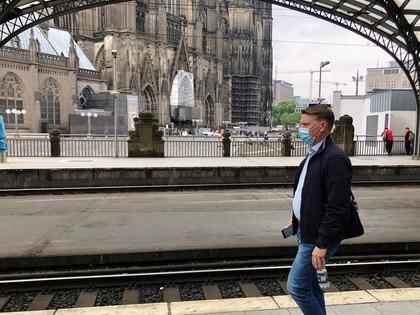 Un pasajero con una máscara protectora camina en un andén cerca de una famosa catedral gótica en Colonia, Alemania, el 10 de junio de 2020 (REUTERS/Gabriela Baczynska)