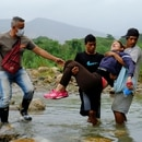 Men carry a woman across the Tachira river, through an illegal crossing near the Colombian-Venezuelan border, after the Colombian government decided to close the Simon Bolivar international bridge as a preventive measure against the spread of the coronavirus disease (COVID-19), in Cucuta, Colombia March 14, 2020. REUTERS/Ferley Ospina. NO RESALES. NO ARCHIVES.