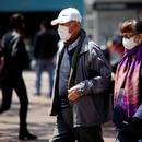 People walk on the street, wearing protective masks as a preventive measure against the spread of the coronavirus disease (COVID-19), in Bogota, Colombia March 17, 2020. REUTERS/Leonardo Munoz. NO RESALES. NO ARCHIVES.