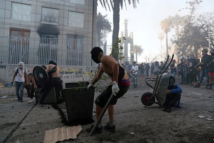 La gente participa en una protesta contra el gobierno de Chile, en el primer aniversario de las protestas y disturbios que sacudieron la capital en 2019, en Santiago, Chile. REUTERS/Ivan Alvarado