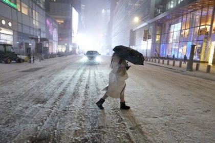 Una persona bajo la nieve en Times Square en Nueva York (TIMOTHY A. CLARY / AFP)