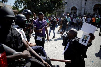 Un abogado se arrodilla ante los agentes de la Policía Nacional de Haití (PNH) en el exterior de la iglesia de Saint Pierre durante una ceremonia religiosa organizada por el Colegio de Abogados para honrar a Monferrier Dorval, asesinado el 28 de agosto en Puerto Príncipe, Haití, el 18 de septiembre de 2020 (REUTERS/Andrés Martínez Casares)