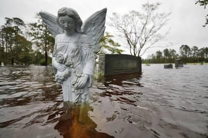 FOTO DE ARCHIVO: Una estatua de un ángel está parcialmente sumergida por las aguas de la inundación en el cementerio de una iglesia donde los residentes se refugiaron y luego fueron evacuados, después del huracán Florence en Leland, Carolina del Norte, el 16 de septiembre de 2018. (REUTERS / Jonathan Drake / Foto de archivo)
