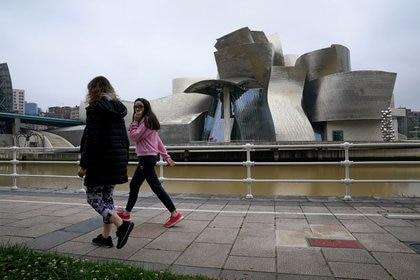 Una familia camina frente al Museo Guggenheim a fines de abril, cuando se levantaron algunas restricciones en la ciudad de Bilbao, en el País Vasco después seis semanas de cuarentena (REUTERS/Vincent West)