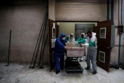 Empleados de un funeral en la capital llevan el cuerpo de una persona que falleció por COVID-19  (Foto: Reuters/Carlos Jasso)