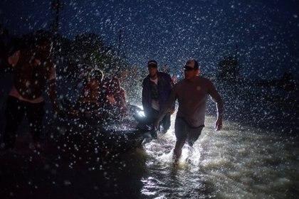 Vecinos ayudan a empujar un bote con evacuados por la tormenta (Reuters)