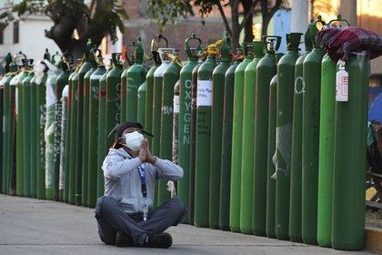 Alejandro Ccasa reza después de esperar días junto a un tanque de oxígeno vacío para su tío que tiene COVID-19 afuera de una tienda de recarga en Callao (AP Foto/Martín Mejía)