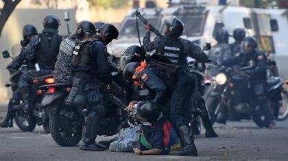 La Guardia Nacional Bolivariana reprimiendo a manifestantes en una marcha en Venezuela (Federico PARRA / AFP)