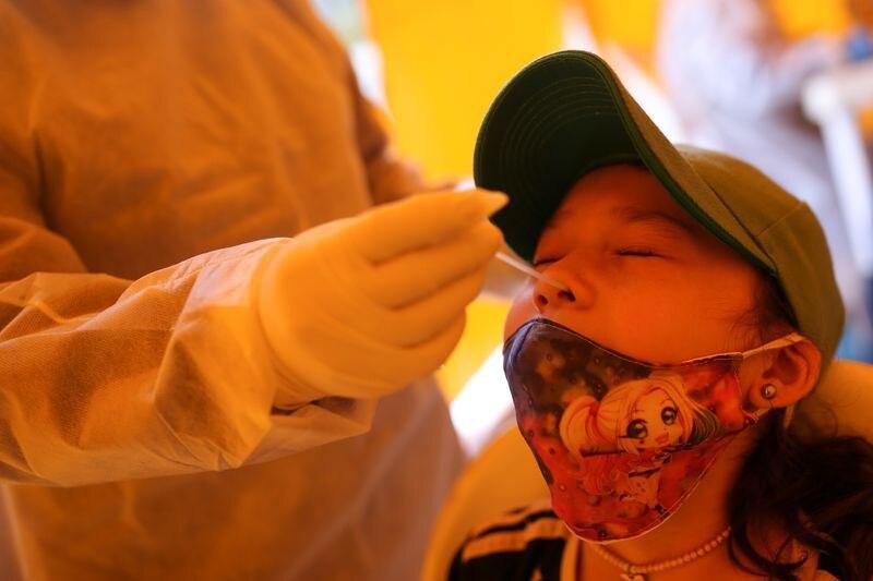 Foto de archivo. Un integrante de un equipo médico toma una muestra para detectar COVID-19 a una niña en Bogotá, Colombia, 1 de julio, 2020. REUTERS/Luisa González