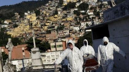 Sepultureros llevan el ataúd de Avelino Fernandes Filho, de 74 años, quien falleció por coronavirus en Río de Janeiro, Brasil. 18 de mayo de 2020 (REUTERS/Ricardo Moraes)