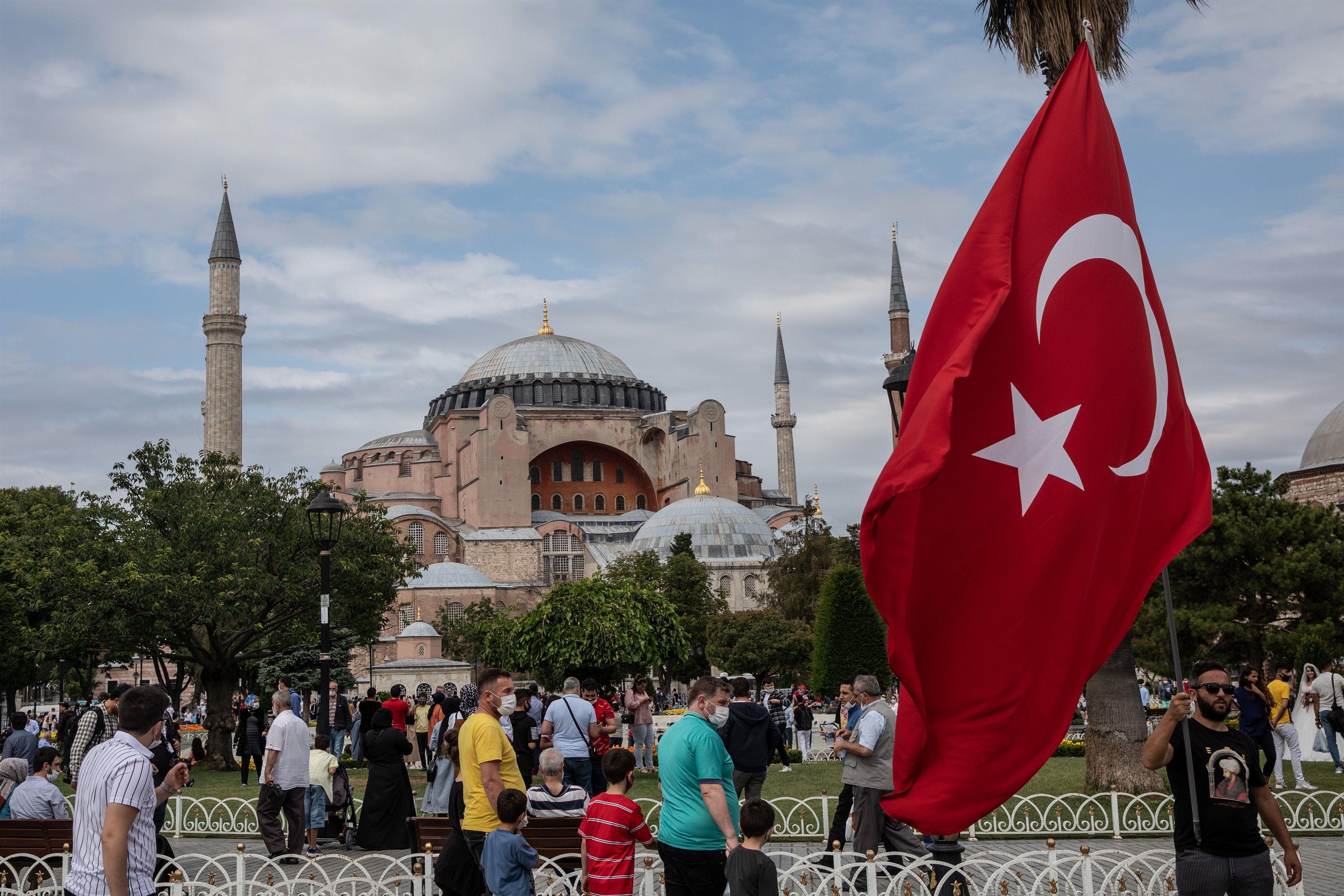 15/07/2020 Un hombre agita la bandera nacional de Turquía frente a la Mezquita de Santa Sofía en el cuarto aniversario del fallido intento de golpe del 15 de julio de 2016. POLITICA  CHRIS MCGRATH