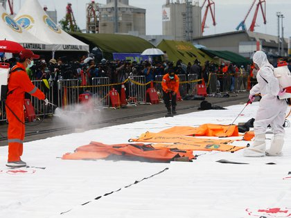 Personal de la Cruz Roja aplica desinfectante en bolsas para cadáveres, a la espera del traslado de los restos (Reuters)