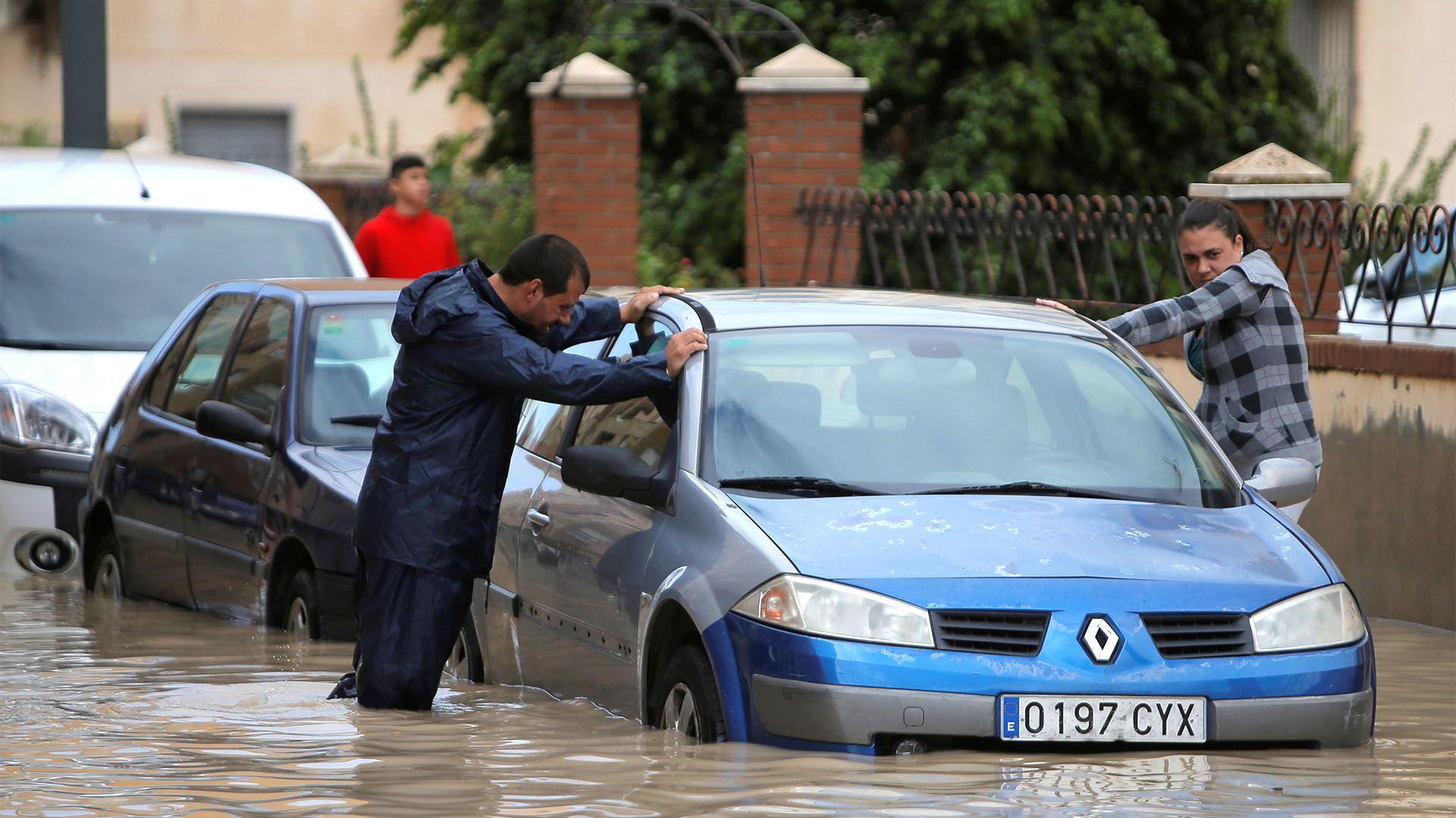 La gente es vista junto a un coche parcialmente sumergido cuando las lluvias torrenciales golpearon Orihuela, España, el 13 de septiembre de 2019 (REUTERS/Jon Nazca)