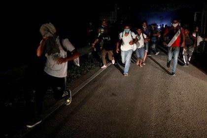 Los migrantes hondureños que buscan llegar a Estados Unidos huyen luego de arrojar piedras a soldados guatemaltecos que bloquearon una carretera para evitar que continuaran hacia la frontera mexicana en San Pedro Cadenas, Guatemala.  2 de octubre de 2020. REUTERS / Luis Echeverría