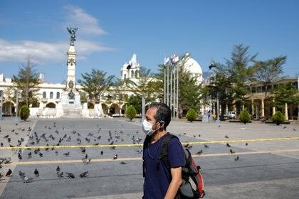 Un hombre camina por la Plaza de la Libertad después de que la municipalidad de San Salvador ordenara cerrar todos los parques de la ciudad para mantener a la gente en sus casas mientras el gobierno toma medidas cada vez más estrictas para prevenir una posible propagación de la enfermedad coronavirus (COVID-19), en San Salvador, El Salvador, el 17 de marzo de 2020 (REUTERS/Jose Cabezas)